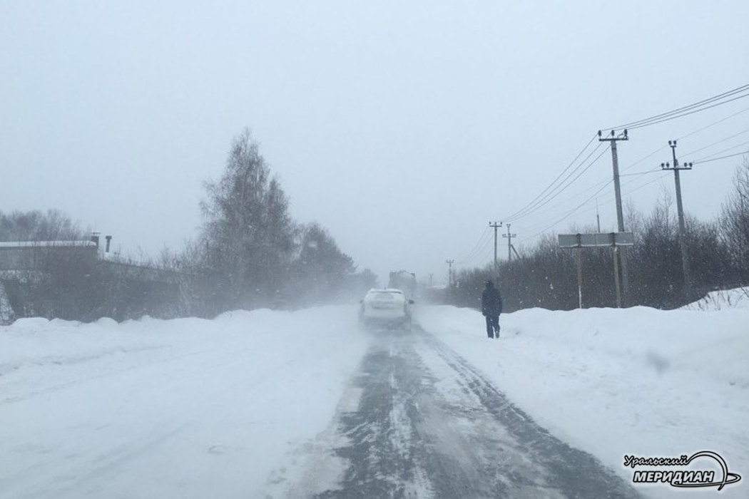 Человек идет по заснеженной дороге